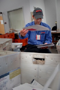 University Mail clerk Kenneth Cash flips a letter into the correct bin while sorting mail. PHOTO BY ROGER WINSTEAD